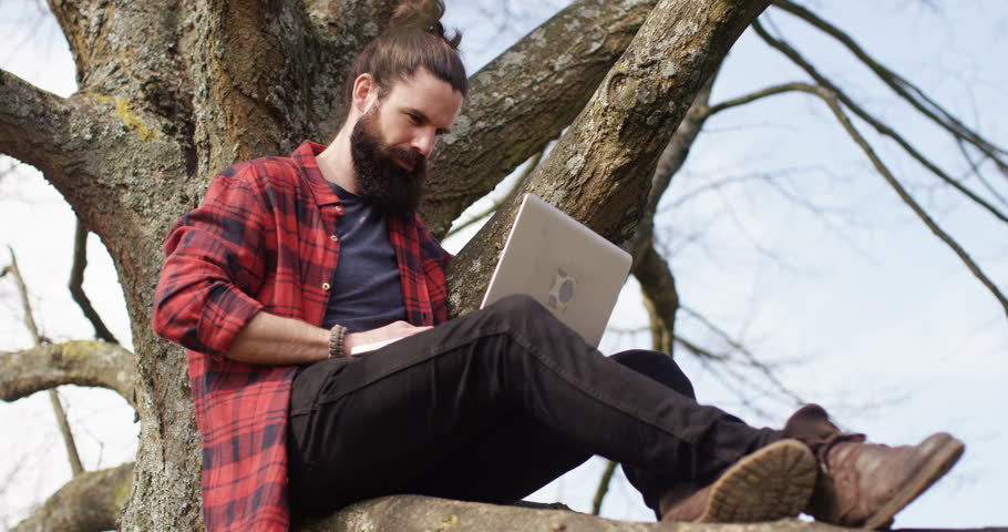 4K Getting back to nature but staying connected through technology. Casual hipster man sitting in a tree & working on laptop computer | Shutterstock HD Video #17036812