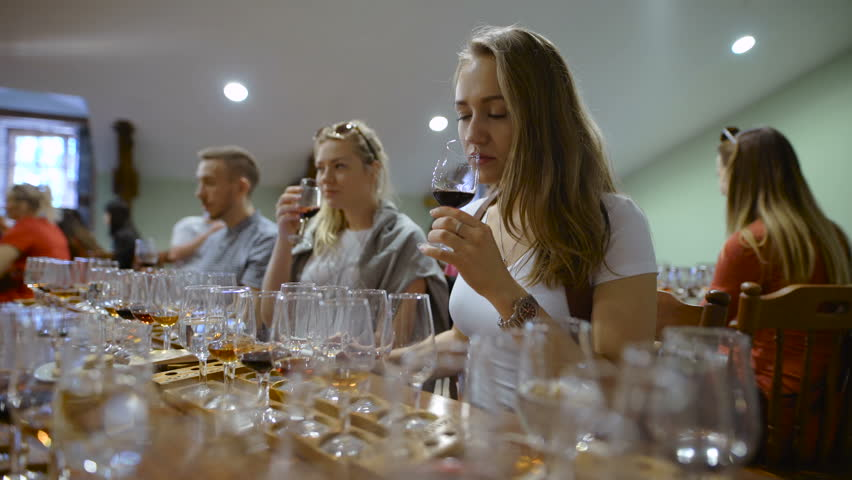 Group of young people on a wine tasting. Girl with a glass of wine, it tastes the drink taste and smell.