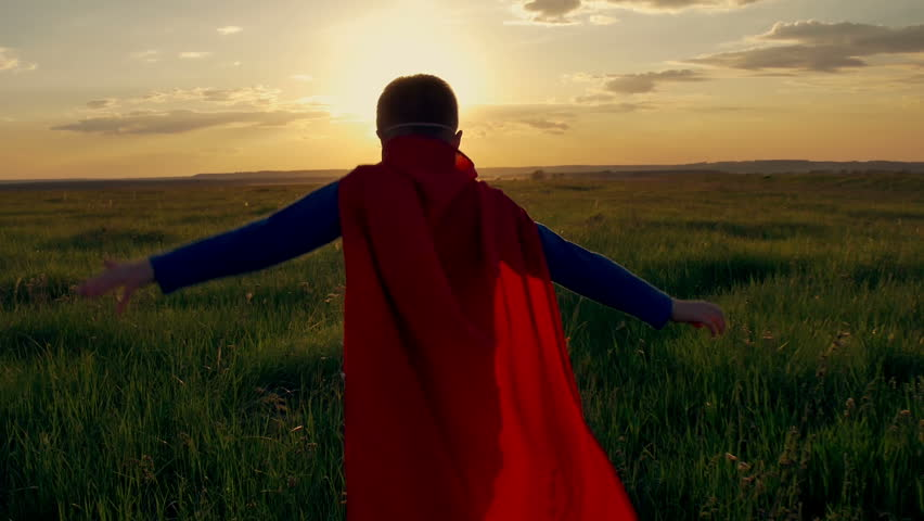 Boy dressed with a Superman cape running in a field, looking into the sunset #17051050