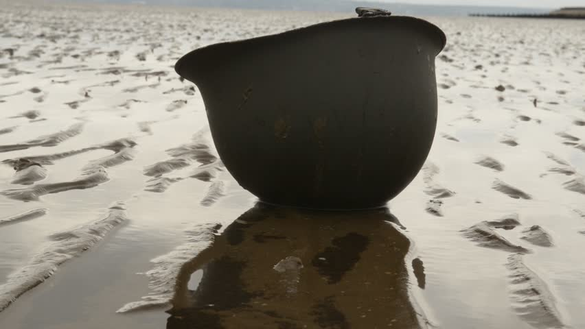 D-Day Landings - American WW2 helmet lies upside down on beach at low tide, with a slight breeze causing ripples on the pools of water.