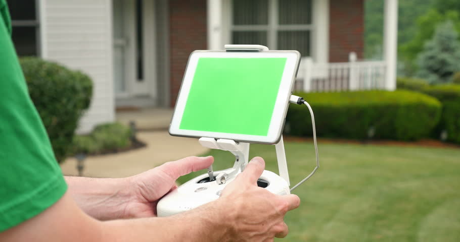 A Man Uses RC Controller For Drone Or UAV Outside House Green Screen Generic Tablet With Optional Corner Markers Advanced Tracking