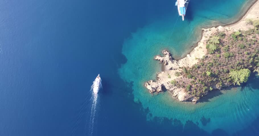 Gocek, Turkey, 2015. 4k aerial footage of the sailboat in the clear blue sea. Camera passes through the island. | Shutterstock HD Video #17109148