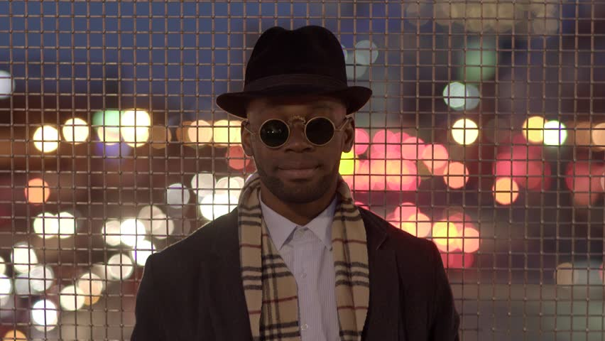 lifestyle portrait of young black man in the city at night. cool guy dressed up with hat and jacket