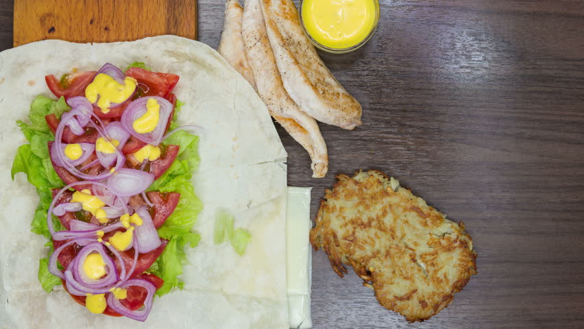 stop motion animation of roll chicken cutlet with potato , lettuce, red onion , tomato and sauce. Cinemagraph, top view #17138254