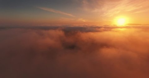 Aerial view of epic low clouds moving over Pacific Coast in California at sunset. Camera flying forward. 4K UHD