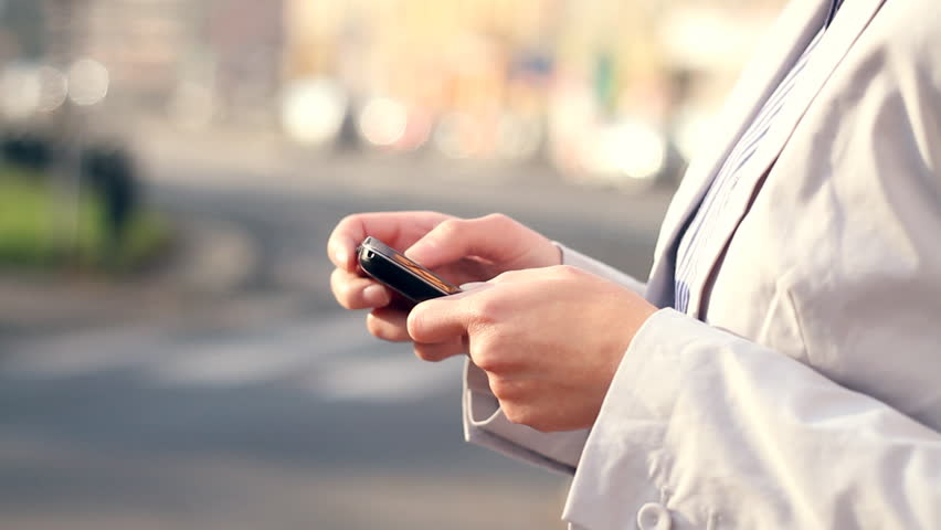 Female hands sending sms, texting by the city street  | Shutterstock HD Video #1719598