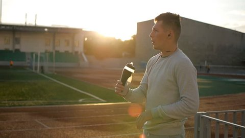 The tired athlete with naseball cap drinks water from the bottle on stadium track