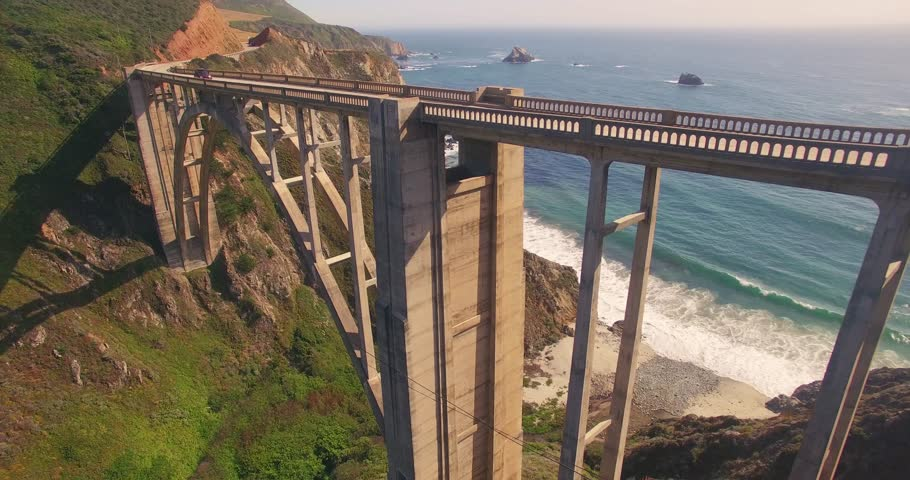 Camera ascending over Bixby Creek Bridge on PCH Highway 1 with Pacific Ocean in background. Monterey, Big Sur, California. 4K UHD aerial view.