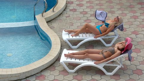 Two smiling women in swimsuits relaxing on sun loungers by private pool at vacation home girlfriends spending their summer vacation together, zoom out long shot high angle view