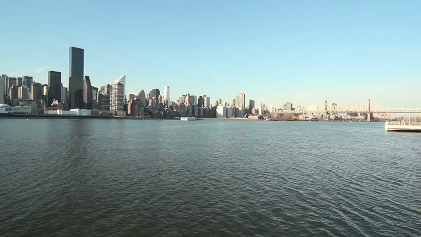Wide angle HD clip of the Manhattan, New York skyline over the East River from Queens panning right to left.