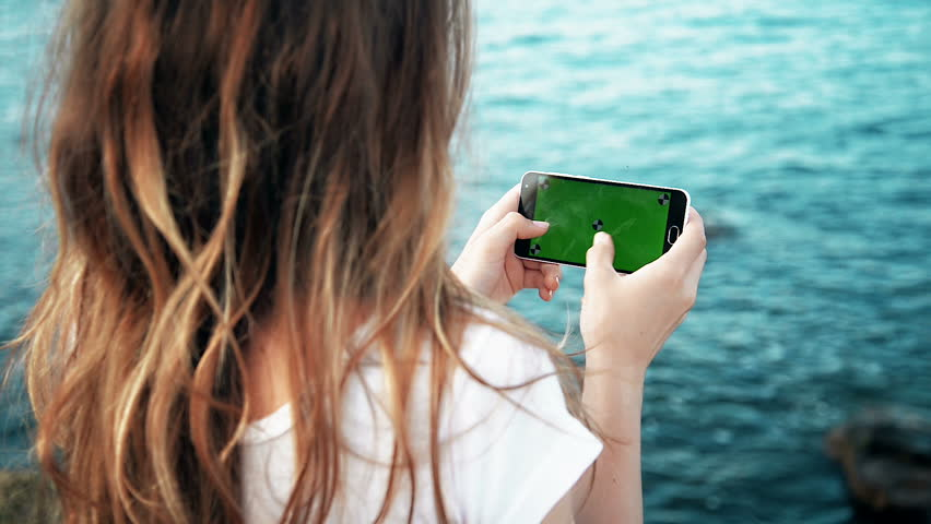 Young Girl is Holding Smartphone with Green Screen at Evening Time Sea | Shutterstock HD Video #17246230