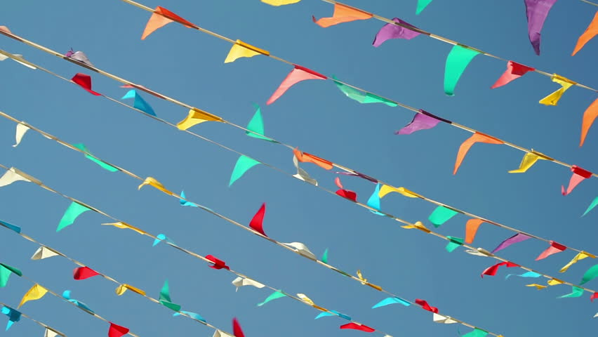 Panning shot against a clear blue sky background of colorful string pennant triangle flags used for celebrations or grand openings blowing in the wind.
