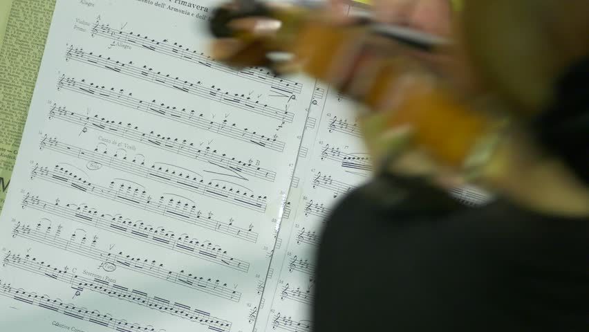 Ungraded: Violinist playing / Violin Player / Orchestra Musician. Female violinist plays violin at a classical music concert against Vivaldi note sheet. Source: Lumix DMC, ungraded. (av24783u)
