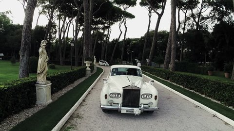 May 2015  White Rolls Royce walking down the street surrounded by greenery. Aerial drone N. Videos about marriage, ceremony, decorations, wreaths, garden,wedding, rolls royce, car,  luxury, lust,