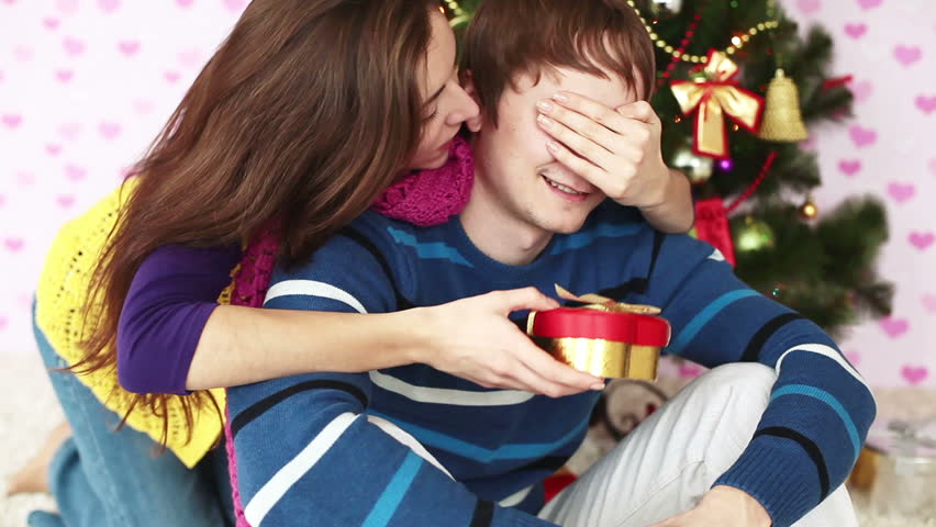 Girl gives her boyfriend a gift near Christmas tree