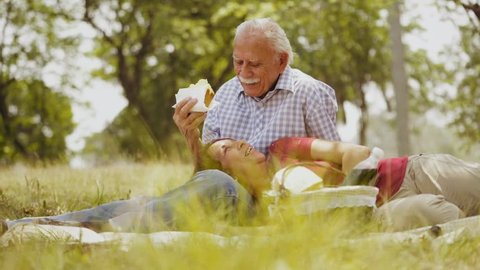Old people, senior couple, elderly man and woman, husband and wife in park, retired seniors, retirement age. Outdoors activities, leisure, fun, recreation. Grandpa and grandma eating food at picnic