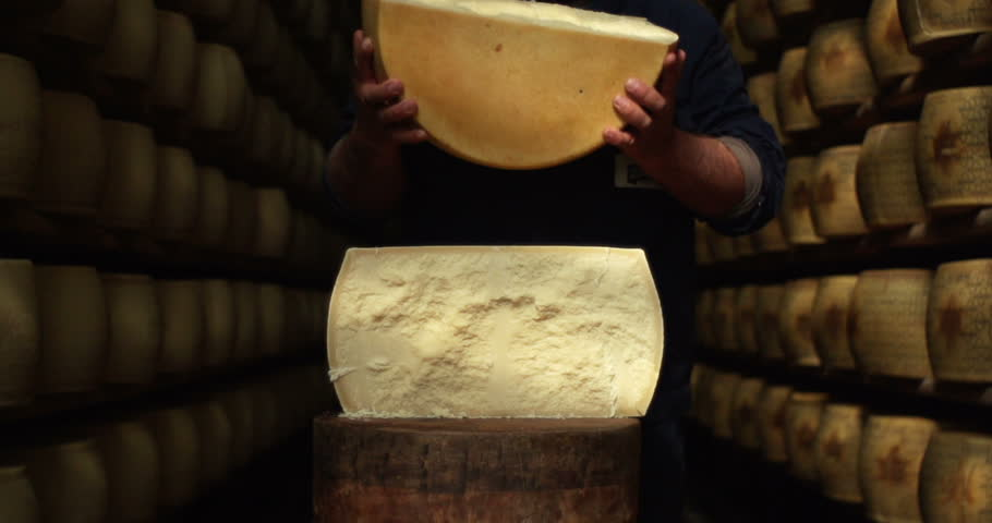 in parma an expert in a Parmesan cheese warehouse opens a form of Parmesan cheese to try it and to see if seasoned correctly