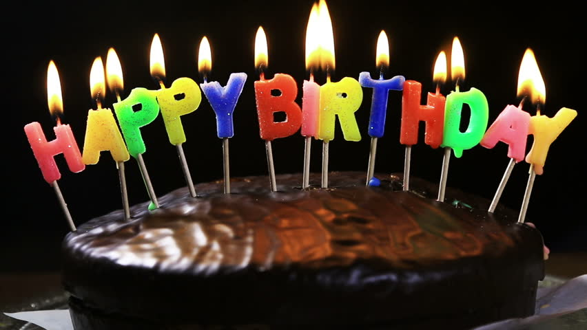 Stock Video Clip of lighted candles on a happy birthday cake