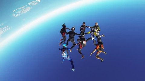Professional skydivers parachuting above coast of Dubai. Formation. Dance. Sunny day.