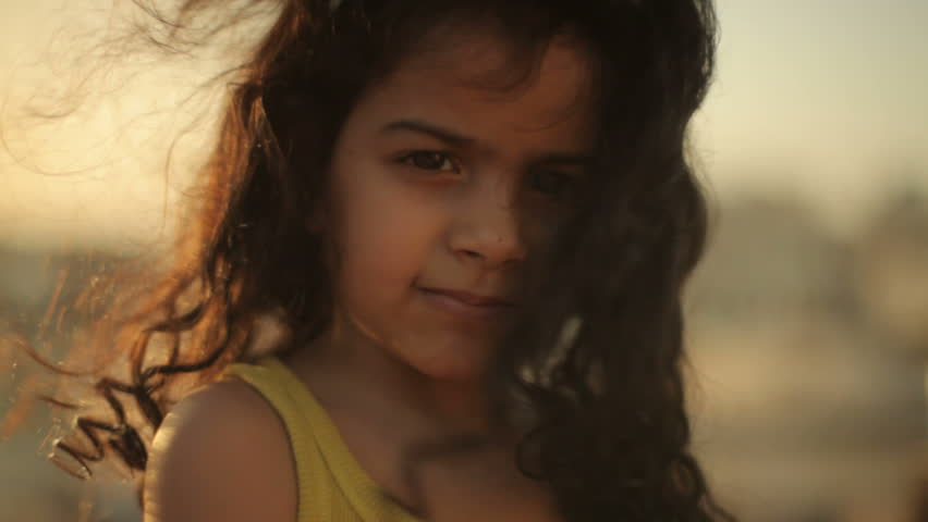 Muharraq, Bahrain - circa 2011 - CU of a little Bahrain girl with long curly hair blowing across her face. She is looking into the camera and smiling.