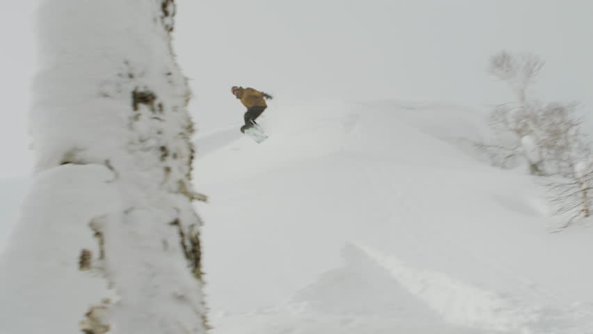 Male Snowboarder Does a Jump, Crashes and Flips in the Powder Snow. Potentially an Injury or Concussion Causing Accident.