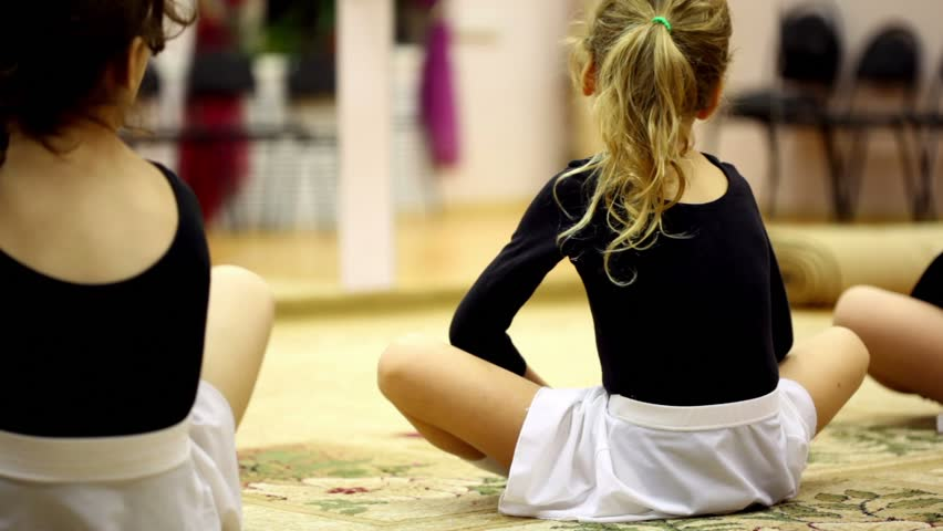 Little girls dressed in ballet clothes sit on floor and stretches risen legs, view from behind