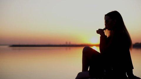 Young beautiful woman smoking ( vaping ) e-cigarette on a sunset beach