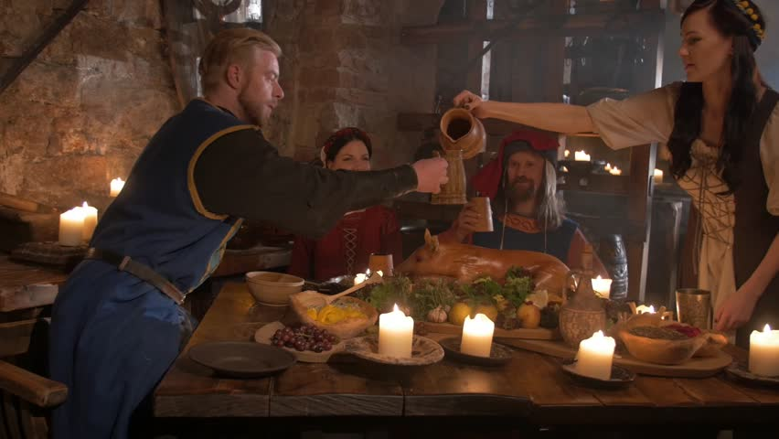 Medieval people eat and drink in ancient castle kitchen interior  in 4K UHD video.