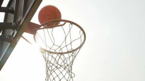 Basketball falls through the net. Low angle shot. Sunbeam.