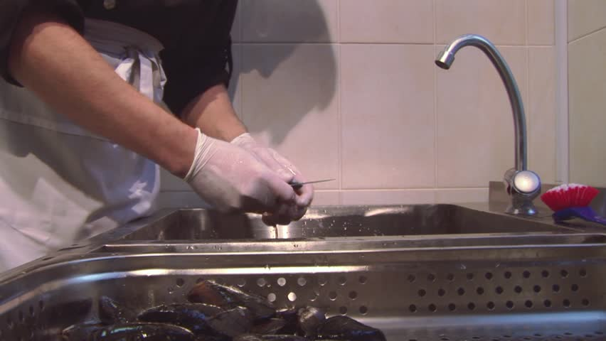 Restaurant Kitchen Gloves cook in gloves, uniform scrub washed mussels in sink with dirty