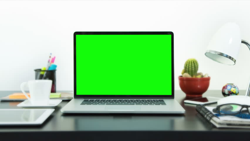 Black desk with a laptop, cell phone and digital tablet. Chroma key. Perfect to put your own images or videos. Track with perspective corner pin.