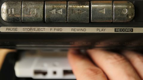 Man's hand inserting the audio cassette into the retro tape player.