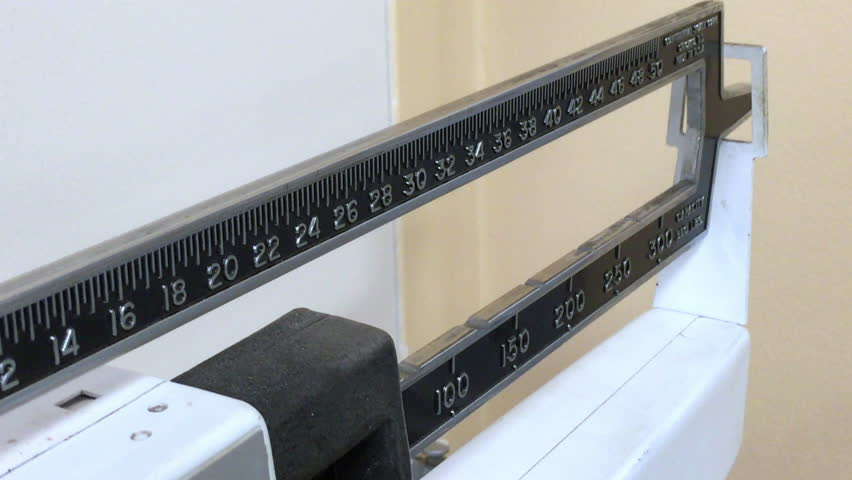 Average woman weighs herself on a manual scale | Shutterstock HD Video #17440000