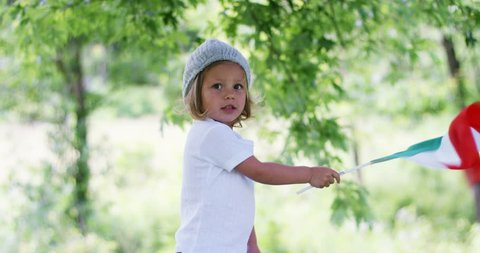 little girl waves a Italian flag surrounded by nature . concept of Italy and hand-made products concept of healthy and fair sport slow motion of the italian flag
