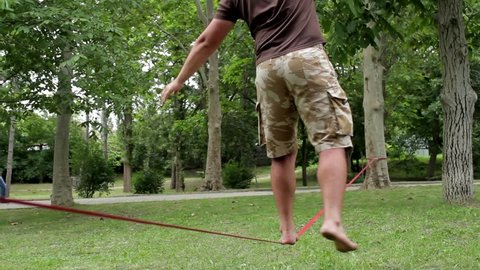 man walking on a tightrope in the park