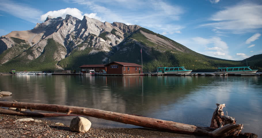 Banff National Park, Alberta, Canada - Lake Minnewanka with boat pier, Mountains and forest at lakeside and clouds at blue sky - Timelapse with motion - October 2014