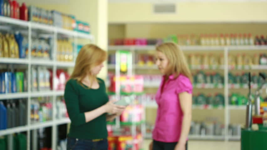 Seller in the store helps girl to choose engine oil. | Shutterstock HD Video #17482576