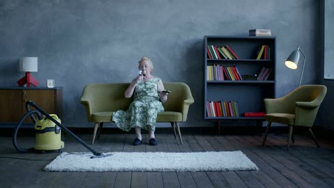 happy elderly woman gave up the cleaning and sat down to relax, drink wine and watch TV