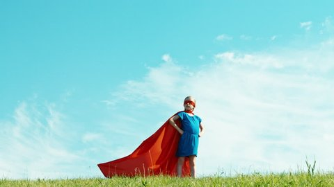 Powerful superhero girl child 7-8 years old protects the world against the blue sky