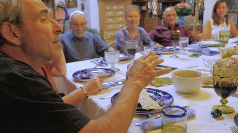 An elder man explains the significance of Matzah at a passover seder - hand held
