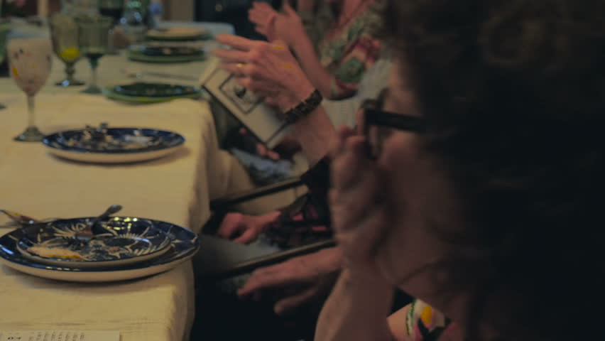 People clapping their hands at a dinner table as a woman laughs and tells a story at a dinner party or passover seder