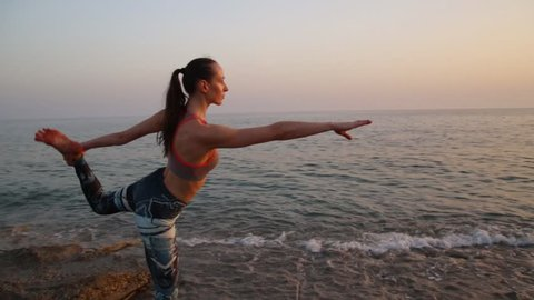I'm shocked how this sportive caucasian woman makes this yoga exercise. And she is alone on the beach of Mediterranean Sea at sunset in perfect light condition, by the way. Healthy lifestyle, you know