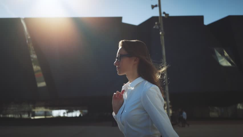 Side view of young successful businesswoman wearing modern suit and walking in the city at break, flare light, sunshine,  slow motion