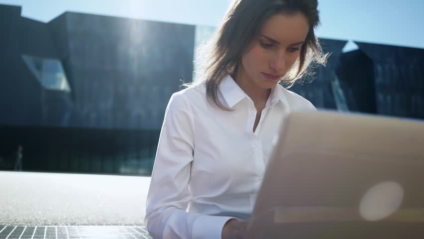 Close-up of young professional businesswoman using her laptop outside while working at modern business center, modern buildings in the background, flare light, film effects,  slow motion | Shutterstock HD Video #17524684