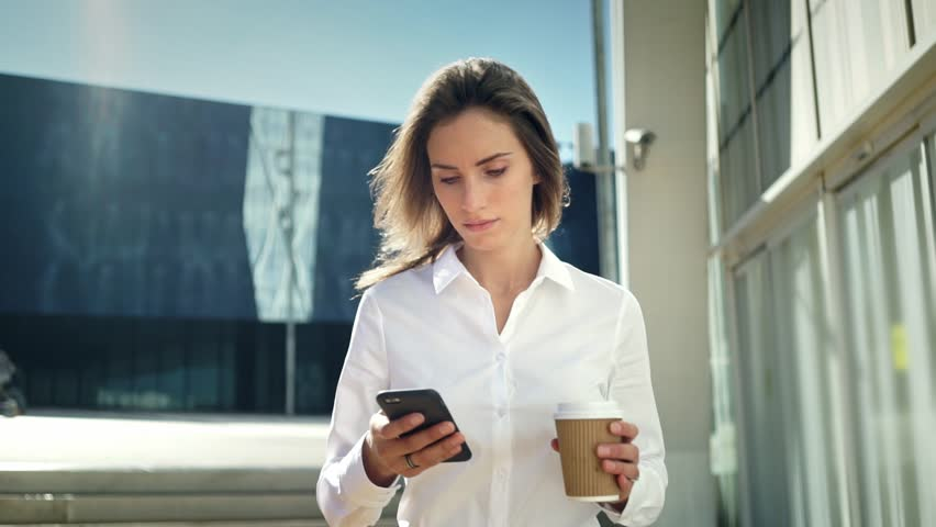 Beautiful young businesswoman wearing white shirt and using modern smart phone while walking at break in the city, professional female employer typing text message on cellphone outside, slow motion