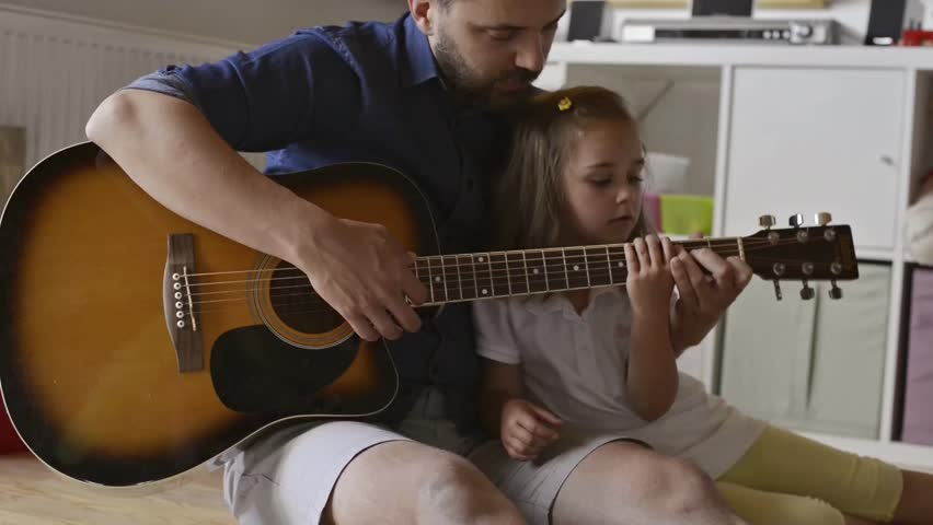 Father and daughter playing guitar, sitting on the floor   Shutterstock HD Video #17531284
