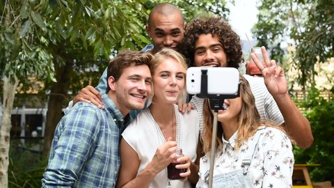 71dd18ff255b6 Happy friends friends looking on smart phone the selfies done. Group of  smiling guys and