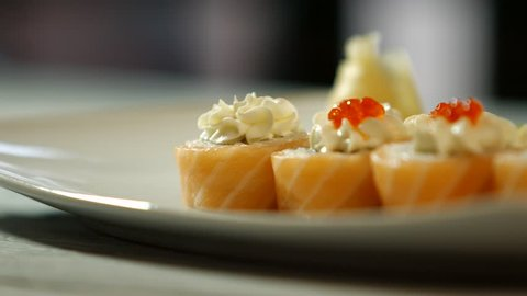 Spoon puts caviar onto sushi. White plate with sushi rolls. Salty caviar and raw fish. Wonders of japanese cuisine.