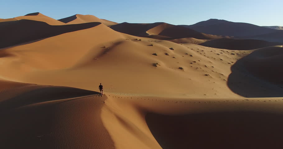 4K aerial view of male tourist walking over the sand dunes in the Namib desert inside the Namib-Naukluft National Park | Shutterstock HD Video #17540890