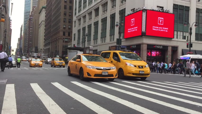 Slow motion shot of 7th avenue traffic on a busy morning commute. An african american male hails a cab and enters a taxi downtown. Outside of Penn Station in midtown Manhattan (New York City-June2016)
